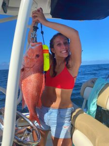unusual fish and game meal. Girl holds up a large red snapper on a boat